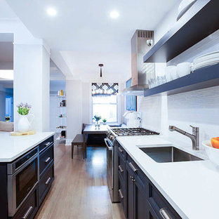 Photo of a large classic galley kitchen/diner in New York with a submerged sink, recessed-panel cabinets, blue cabinets, wood worktops, white splashback, metro tiled splashback, stainless steel appliances, plywood flooring and an island.