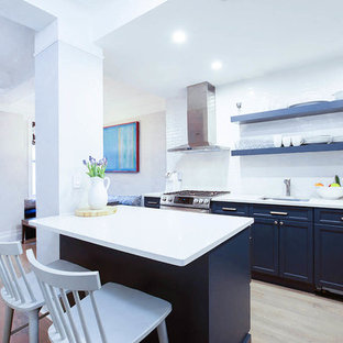 Design ideas for a large traditional galley kitchen/diner in New York with a submerged sink, recessed-panel cabinets, blue cabinets, wood worktops, white splashback, metro tiled splashback, stainless steel appliances, plywood flooring and an island.