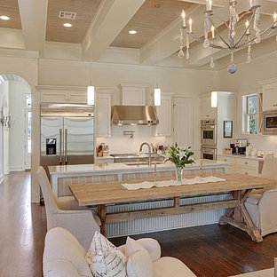 Transitional eat-in kitchen pictures - Eat-in kitchen - transitional l-shaped eat-in kitchen idea in New Orleans with an undermount sink, white cabinets, marble countertops, white backsplash and subway tile backsplash