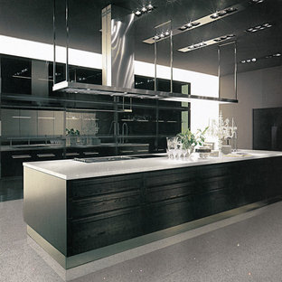Diseño de cocina de galera, minimalista, de tamaño medio, abierta, con armarios con paneles lisos, puertas de armario negras, encimera de cuarcita, electrodomésticos de acero inoxidable, suelo de mármol y una isla