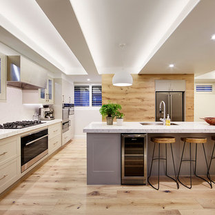 Large contemporary eat-in kitchen in Melbourne with an undermount sink, recessed-panel cabinets, grey cabinets, quartz benchtops, stone slab splashback, stainless steel appliances, light hardwood floors and an island.