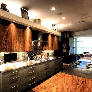 Idées déco pour une grande cuisine ouverte parallèle éclectique avec un évier 3 bacs, un placard à porte plane, des portes de placard en bois brun, un plan de travail en bois, une crédence multicolore, un électroménager en acier inoxydable et un sol en bois brun.