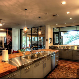 Design ideas for a large eclectic galley open plan kitchen in Austin with a triple-bowl sink, flat-panel cabinets, grey cabinets, wood benchtops, beige splashback and stainless steel appliances.