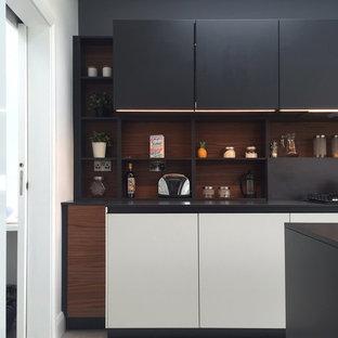 ダブリンのコンテンポラリースタイルのおしゃれなキッチン (フラットパネル扉のキャビネット、グレーのキャビネット、ラミネートカウンター、グレーのキッチンパネル、黒い調理設備、リノリウムの床) の写真