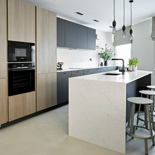 Photo of a small contemporary kitchen in London with a submerged sink, flat-panel cabinets, marble worktops, black appliances, an island, grey floors, white worktops, black cabinets and concrete flooring.