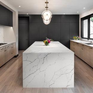 Modern inredning av ett avskilt flerfärgad flerfärgat u-kök, med en undermonterad diskho, släta luckor, skåp i mellenmörkt trä, bänkskiva i kvarts, flerfärgad stänkskydd, integrerade vitvaror, mellanmörkt trägolv, en köksö och brunt golv