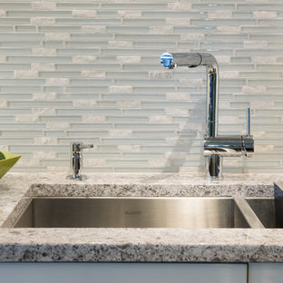 Small contemporary eat-in kitchen designs - Eat-in kitchen - small contemporary single-wall eat-in kitchen idea in Minneapolis with an undermount sink, flat-panel cabinets, white cabinets, quartz countertops, multicolored backsplash, glass sheet backsplash, black appliances and two islands