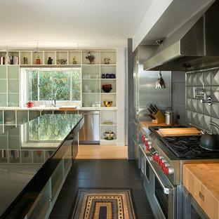 Photo of a medium sized contemporary l-shaped open plan kitchen in Phoenix with granite worktops, metallic splashback, metal splashback, stainless steel appliances, an island and black floors.