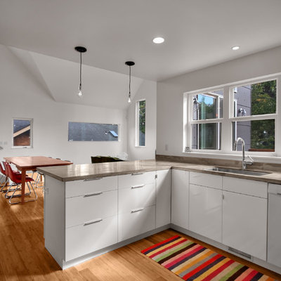 Minimalist eat-in kitchen photo in Seattle with white appliances, a single-bowl sink, flat-panel cabinets and white cabinets
