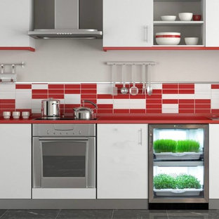 Design ideas for a mid-sized contemporary single-wall separate kitchen in New York with a drop-in sink, flat-panel cabinets, white cabinets, solid surface benchtops, multi-coloured splashback, mosaic tile splashback, stainless steel appliances, porcelain floors, no island, grey floor and red benchtop.