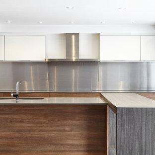 Midcentury galley open plan kitchen in Toronto with an undermount sink, flat-panel cabinets, medium wood cabinets, quartz benchtops, metallic splashback, metal splashback, panelled appliances, vinyl floors and a peninsula.