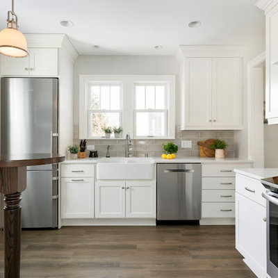 Kitchen - small country l-shaped medium tone wood floor and brown floor kitchen idea in Minneapolis with a farmhouse sink, shaker cabinets, white cabinets, gray backsplash, subway tile backsplash, stainless steel appliances, a peninsula and white countertops
