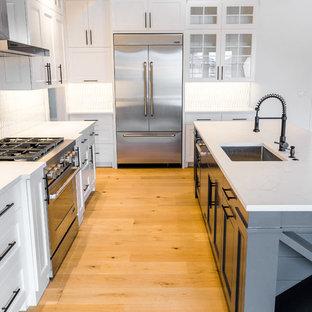Inredning av ett lantligt mellanstort kök, med en undermonterad diskho, luckor med infälld panel, vita skåp, bänkskiva i kvarts, vitt stänkskydd, stänkskydd i keramik, rostfria vitvaror, ljust trägolv, en köksö och flerfärgat golv