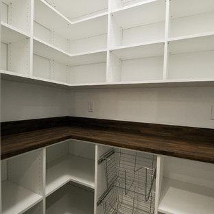 Lantlig inredning av ett kök, med en undermonterad diskho, skåp i shakerstil, vita skåp, bänkskiva i kvarts, vitt stänkskydd, stänkskydd i keramik, rostfria vitvaror, laminatgolv, en köksö och brunt golv