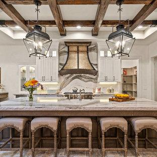 Klassisk inredning av ett beige beige l-kök, med en rustik diskho, luckor med upphöjd panel, vita skåp, marmorbänkskiva, beige stänkskydd, stänkskydd i marmor, rostfria vitvaror och en köksö