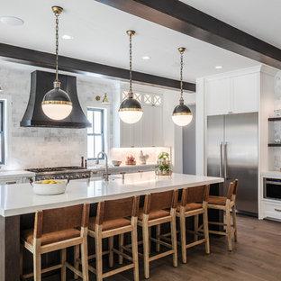サンフランシスコの大きいトランジショナルスタイルのおしゃれなキッチン (エプロンフロントシンク、シェーカースタイル扉のキャビネット、白いキャビネット、クオーツストーンカウンター、グレーのキッチンパネル、大理石の床、シルバーの調理設備の、無垢フローリング、茶色い床、白いキッチンカウンター) の写真