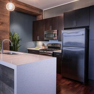シカゴの小さいコンテンポラリースタイルのおしゃれなキッチン (ダブルシンク、フラットパネル扉のキャビネット、茶色いキャビネット、クオーツストーンカウンター、青いキッチンパネル、ガラスタイルのキッチンパネル、シルバーの調理設備、無垢フローリング) の写真
