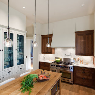 Inspiration for a timeless enclosed kitchen remodel in Austin with stainless steel appliances, wood countertops, dark wood cabinets, white backsplash and stone slab backsplash