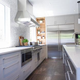 トロントの大きいコンテンポラリースタイルのおしゃれなキッチン (アンダーカウンターシンク、フラットパネル扉のキャビネット、グレーのキャビネット、クオーツストーンカウンター、グレーのキッチンパネル、石タイルのキッチンパネル、シルバーの調理設備の、磁器タイルの床) の写真