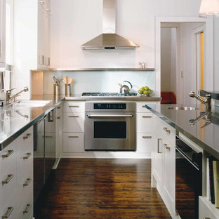 Inspiration for a contemporary l-shaped kitchen/diner in Minneapolis with a submerged sink, flat-panel cabinets, white cabinets, stainless steel worktops, metallic splashback, stainless steel appliances, dark hardwood flooring, metal splashback and an island.