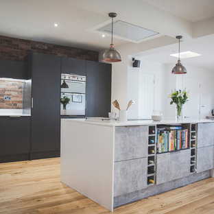 Design ideas for a contemporary l-shaped kitchen/diner in Devon with flat-panel cabinets, grey cabinets, an island, red splashback, stainless steel appliances, medium hardwood flooring and brown floors.