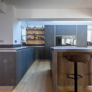 Idée de décoration pour une cuisine ouverte parallèle urbaine de taille moyenne avec un placard à porte plane, des portes de placard grises, un plan de travail en carrelage, un îlot central et un plan de travail gris.