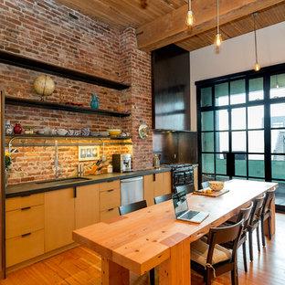 シアトルのインダストリアルスタイルのおしゃれなキッチン (アンダーカウンターシンク、フラットパネル扉のキャビネット、中間色木目調キャビネット、シルバーの調理設備、無垢フローリング) の写真
