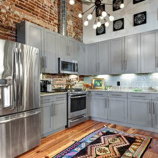 チャールストンのインダストリアルスタイルのおしゃれなコの字型キッチン (シェーカースタイル扉のキャビネット、グレーのキャビネット、グレーのキッチンパネル、サブウェイタイルのキッチンパネル、シルバーの調理設備の、無垢フローリング、マルチカラーのキッチンカウンター) の写真
