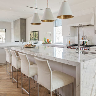 Trendy l-shaped medium tone wood floor and beige floor kitchen photo in Houston with an undermount sink, flat-panel cabinets, white cabinets, white backsplash, stainless steel appliances and an island