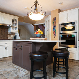 Inspiration for a mid-sized traditional u-shaped eat-in kitchen in Calgary with raised-panel cabinets, white cabinets, quartz benchtops, with island, multi-coloured floor, white benchtop, beige splashback, slate splashback, stainless steel appliances and porcelain floors.
