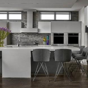 シカゴの広いコンテンポラリースタイルのおしゃれなキッチン (シングルシンク、フラットパネル扉のキャビネット、グレーのキャビネット、珪岩カウンター、グレーのキッチンパネル、レンガのキッチンパネル、シルバーの調理設備、濃色無垢フローリング、茶色い床、グレーのキッチンカウンター) の写真