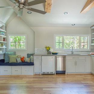 Inredning av ett klassiskt mellanstort l-kök, med ljust trägolv, en undermonterad diskho, skåp i shakerstil, vita skåp, stänkskydd med metallisk yta, stänkskydd i mosaik och rostfria vitvaror