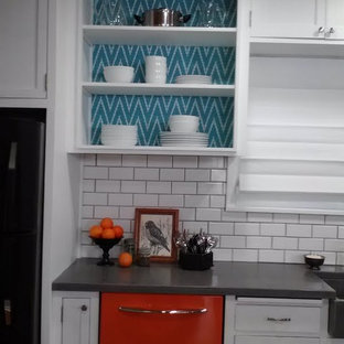 This is an example of a mid-sized country galley eat-in kitchen in Minneapolis with an integrated sink, open cabinets, white cabinets, concrete benchtops, white splashback, subway tile splashback, coloured appliances, cork floors and with island.