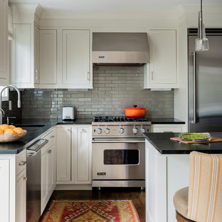 Transitional kitchen appliance - Example of a transitional l-shaped dark wood floor kitchen design in Boston with an undermount sink, shaker cabinets, white cabinets, gray backsplash, subway tile backsplash, stainless steel appliances and an island
