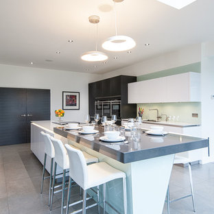 Inspiration for a large contemporary single-wall eat-in kitchen in London with flat-panel cabinets, grey cabinets, stainless steel appliances, with island, an undermount sink, white splashback, glass sheet splashback and porcelain floors.