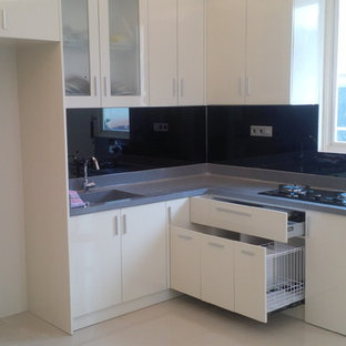 Small asian l-shaped kitchen pantry in Other with a drop-in sink, flat-panel cabinets, white cabinets, solid surface benchtops, black splashback, glass sheet splashback, black appliances, marble floors and no island.