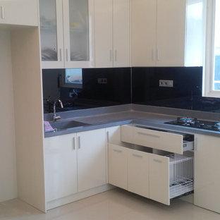 他の地域の小さいアジアンスタイルのおしゃれなキッチン (ドロップインシンク、フラットパネル扉のキャビネット、白いキャビネット、人工大理石カウンター、黒いキッチンパネル、ガラス板のキッチンパネル、黒い調理設備、大理石の床、アイランドなし) の写真