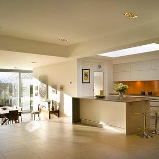 Foto på ett stort funkis kök med öppen planlösning, med en köksö, släta luckor, vita skåp, bänkskiva i koppar, orange stänkskydd, glaspanel som stänkskydd och en undermonterad diskho