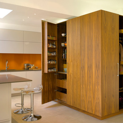 Example of a large trendy kitchen design in London with an island, flat-panel cabinets, medium tone wood cabinets, solid surface countertops, orange backsplash, glass sheet backsplash and an undermount sink