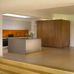 ロンドンの大きいコンテンポラリースタイルのおしゃれなキッチン (フラットパネル扉のキャビネット、白いキャビネット、オレンジのキッチンパネル、ガラス板のキッチンパネル、アンダーカウンターシンク) の写真