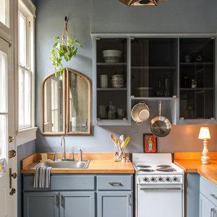 Diseño de cocina en L, clásica, pequeña, con fregadero encastrado, armarios estilo shaker, puertas de armario grises, encimera de madera, electrodomésticos blancos y península