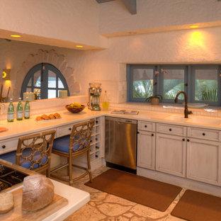 Tropische Küche in U-Form mit Triple-Waschtisch, Schrankfronten mit vertiefter Füllung, weißen Schränken, Quarzit-Arbeitsplatte, Küchenrückwand in Weiß, Halbinsel und beigem Boden in Miami