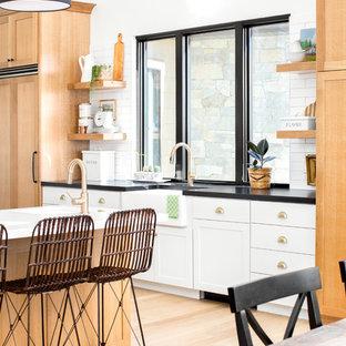 Große Country Wohnküche mit Landhausspüle, Schrankfronten im Shaker-Stil, hellen Holzschränken, Küchenrückwand in Weiß, Rückwand aus Keramikfliesen, Küchengeräten aus Edelstahl, hellem Holzboden, zwei Kücheninseln, beigem Boden, schwarzer Arbeitsplatte und Granit-Arbeitsplatte in Salt Lake City