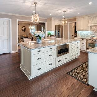 アトランタの広いトラディショナルスタイルのおしゃれなキッチン (アンダーカウンターシンク、レイズドパネル扉のキャビネット、白いキャビネット、御影石カウンター、シルバーの調理設備、竹フローリング、茶色い床、茶色いキッチンパネル、石タイルのキッチンパネル、マルチカラーのキッチンカウンター) の写真