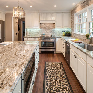 Photo of a large traditional u-shaped eat-in kitchen in Atlanta with an undermount sink, raised-panel cabinets, white cabinets, granite benchtops, brick splashback, stainless steel appliances, bamboo floors, with island, brown floor, brown splashback and multi-coloured benchtop.