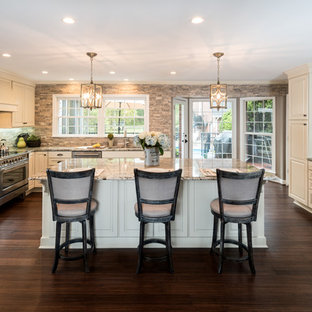 Large traditional u-shaped kitchen in Atlanta with an undermount sink, raised-panel cabinets, granite benchtops, grey splashback, stainless steel appliances, bamboo floors, with island, brown floor, grey benchtop and beige cabinets.