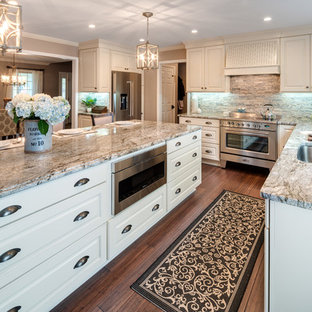 Large traditional u-shaped eat-in kitchen in Atlanta with an undermount sink, raised-panel cabinets, white cabinets, granite benchtops, stainless steel appliances, bamboo floors, with island, brown floor, brown splashback, stone tile splashback and multi-coloured benchtop.