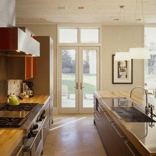 Diseño de cocina contemporánea con electrodomésticos de acero inoxidable, fregadero integrado, armarios con paneles lisos, puertas de armario rojas, salpicadero metalizado, salpicadero de metal y encimera de madera