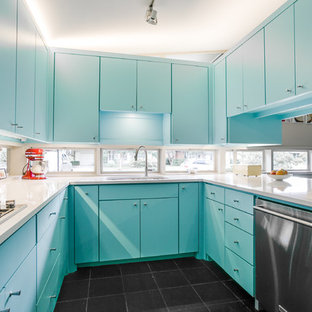 Aménagement d'une cuisine rétro en U fermée et de taille moyenne avec un évier encastré, un placard à porte plane, des portes de placard bleues, un électroménager en acier inoxydable, un plan de travail en quartz modifié, une crédence en fenêtre, un sol en ardoise et un sol noir.