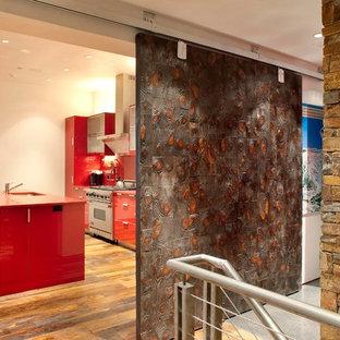 Einzeilige, Mittelgroße Moderne Küche mit Unterbauwaschbecken, flächenbündigen Schrankfronten, roten Schränken, Mineralwerkstoff-Arbeitsplatte, Küchenrückwand in Rot, Glasrückwand, Küchengeräten aus Edelstahl, dunklem Holzboden, Kücheninsel, braunem Boden und roter Arbeitsplatte in Denver